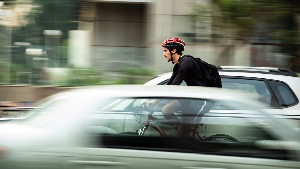 A bicyclist passing a car