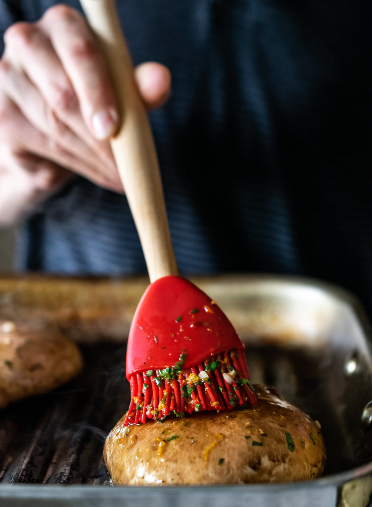 brushing the mushrooms with marinade as they cook