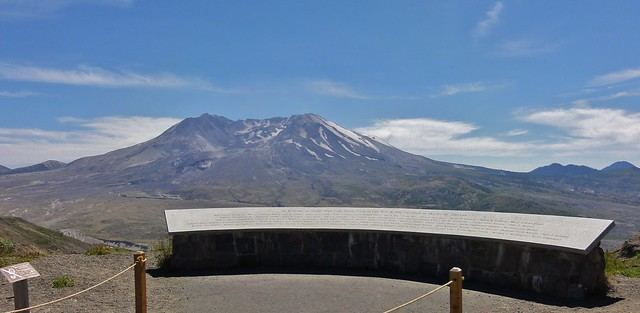 Image shows Mount St. Helens, nearly devoid of snowcap and looking very grim, with the curved granite memorial in front of her.