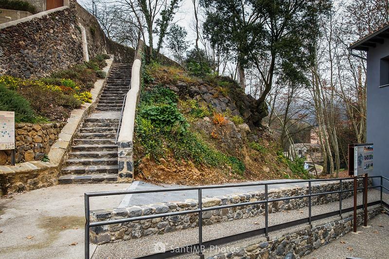 Junto a la Oficina de Turismo de Sant Joan les Fonts, con el Molí Fondo a la derecha y las escaleras de la Ruta de las 3 Coladas enfrente