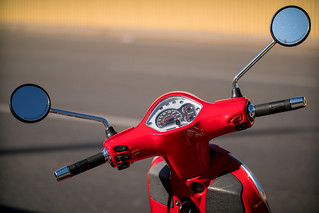Close-up of moped handlebar including speedometer and mirrors