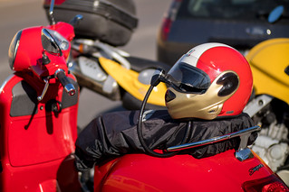 Bike helmet tied to the seat of a moped