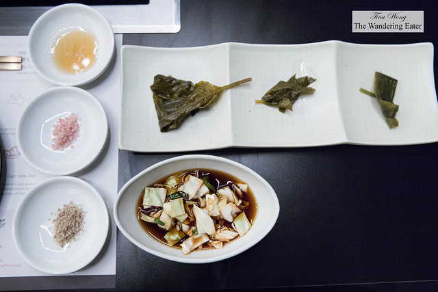 Assortment of salts, Korean pickles (perilla leaf, parsnip leaf, and wild garlic leaf) and cabbage and serrano peppers in light soy sauce