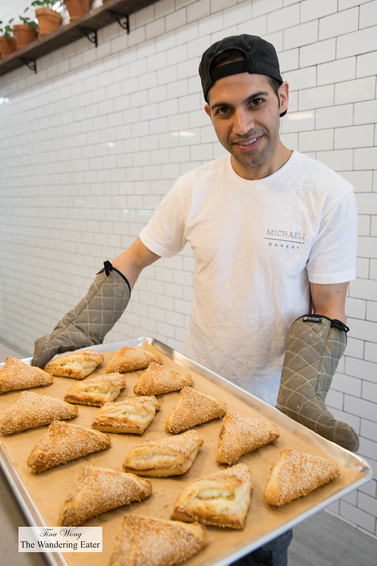 Chef/Owner Adir Michaeli holding a tray of fresh baked potato burekas
