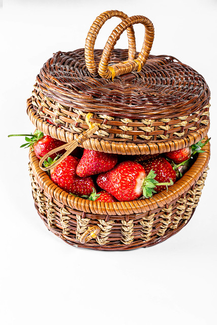 Wicker basket filled with fresh strawberries on white background