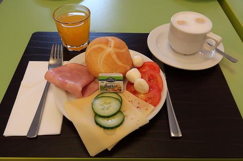 Semmel mit Käse und Kochschinken mit Tomaten, Mozzarellakugeln und Gurken zu Multivitamin-Erfrischungsgetränk und Milchkaffee