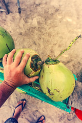Man hand with green fresh coconut