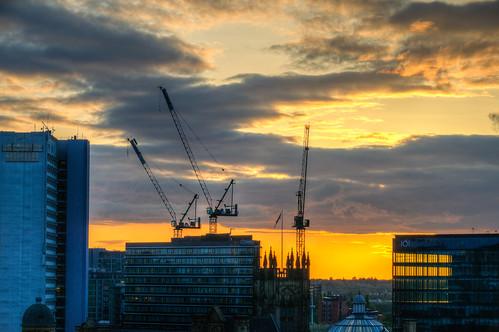 manchester uk unitedkingdom city downtown cityscape manchesteruk europe england crane sun sunset