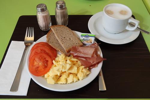 Rührei, roher Schinken, Brot und Tomaten zu Milchkaffee