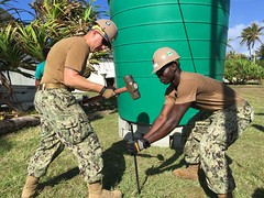 ROI-NAMUR ATOLL, Marshall Islands (May 17, 2019) Steelworker 2nd Class Jacob Grimm and Construction Electrician 2nd Class Billings Amoah, both assigned to Naval Mobile Construction Battalion (NMCB) 4, hammer a metal stake into the ground to secure a water tank. The tank will be used to hold water necessary for the construction of the Ennibur Medical Clinic. NMCB 4 is forward-deployed throughout the Indo-Pacific region ready to support major combat operations, humanitarian assistance and disaster relief and to provide general engineering and civil support to U.S. and joint forces. (U.S. Navy photo by Utilitiesman 3rd Class Ervin Villanueva/Released)
