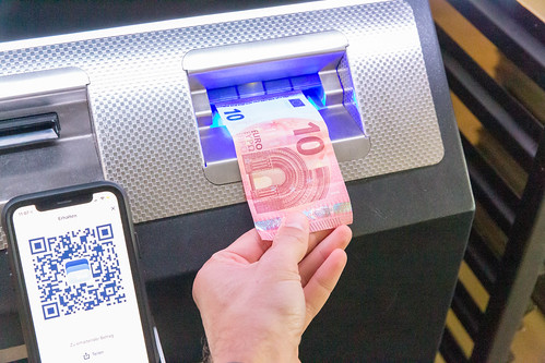 Man puts 10 Euro in a Bitcoin ATM, to transfer Bitcoins to his Smartphone via BlueWallet App | by verchmarco