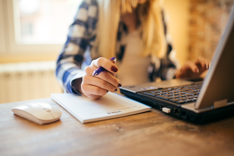 A female hand with pen on notepad, working on laptop in office