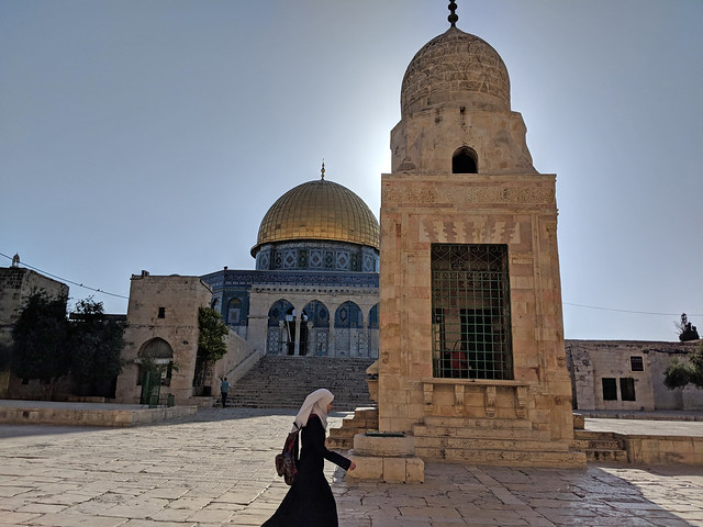 a student takes a shortcut in front of the Dome of the Rock