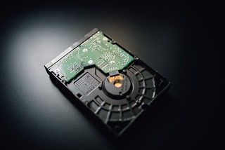 Close-up of a hard disk drive on a black background | by Ivan Radic