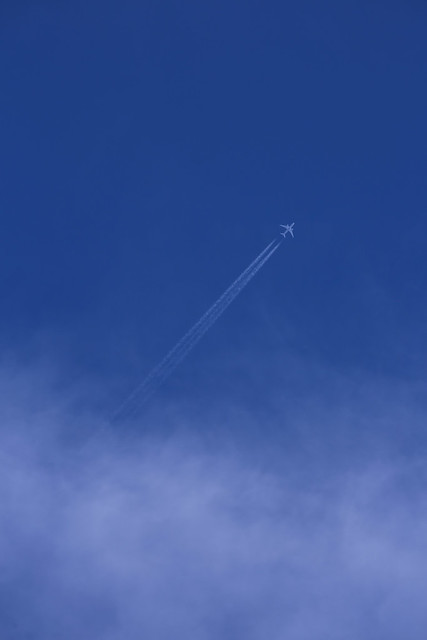 Airplane in the sky w/ contrail - stock photo