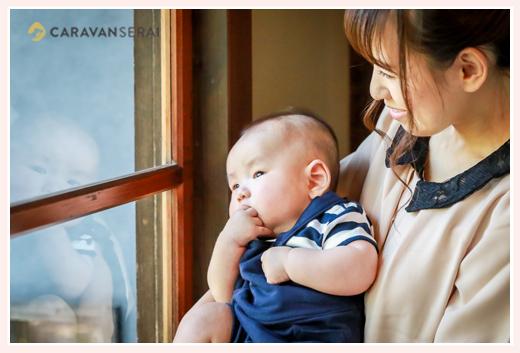 ママに抱っこされ窓の外を眺める3か月の男の子赤ちゃん