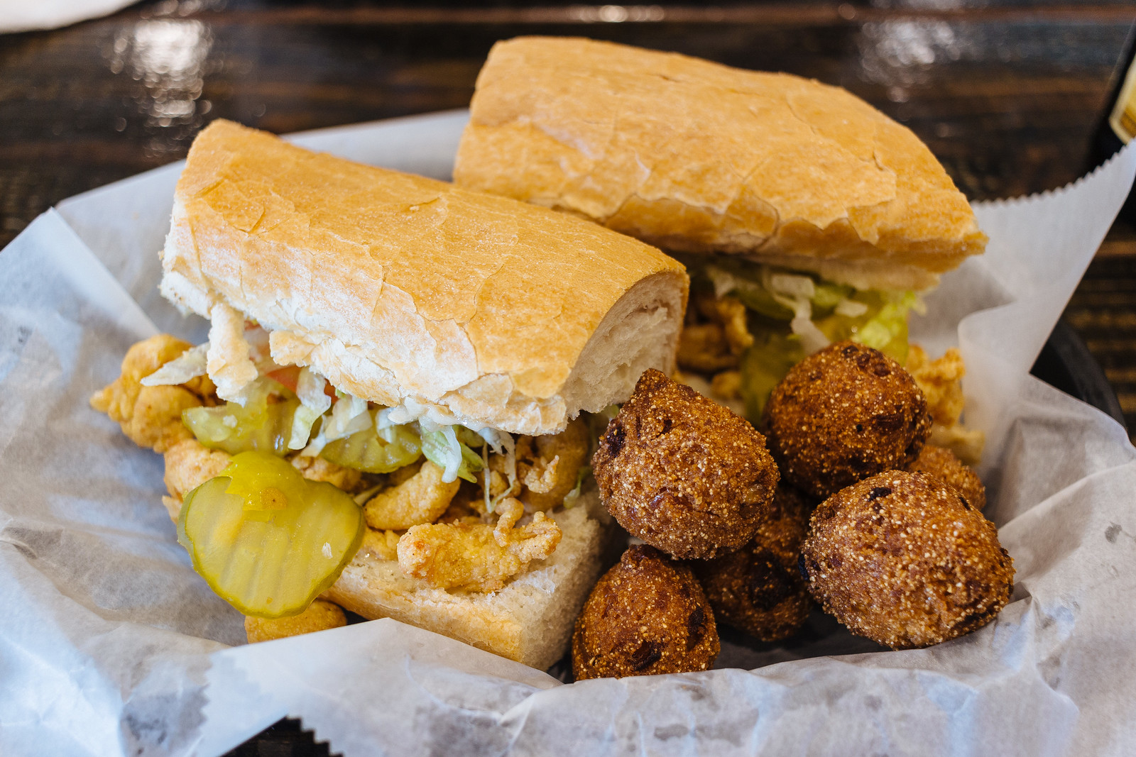 Po'boy sandwich with fried crawfish and pickles with a side of hushpuppies