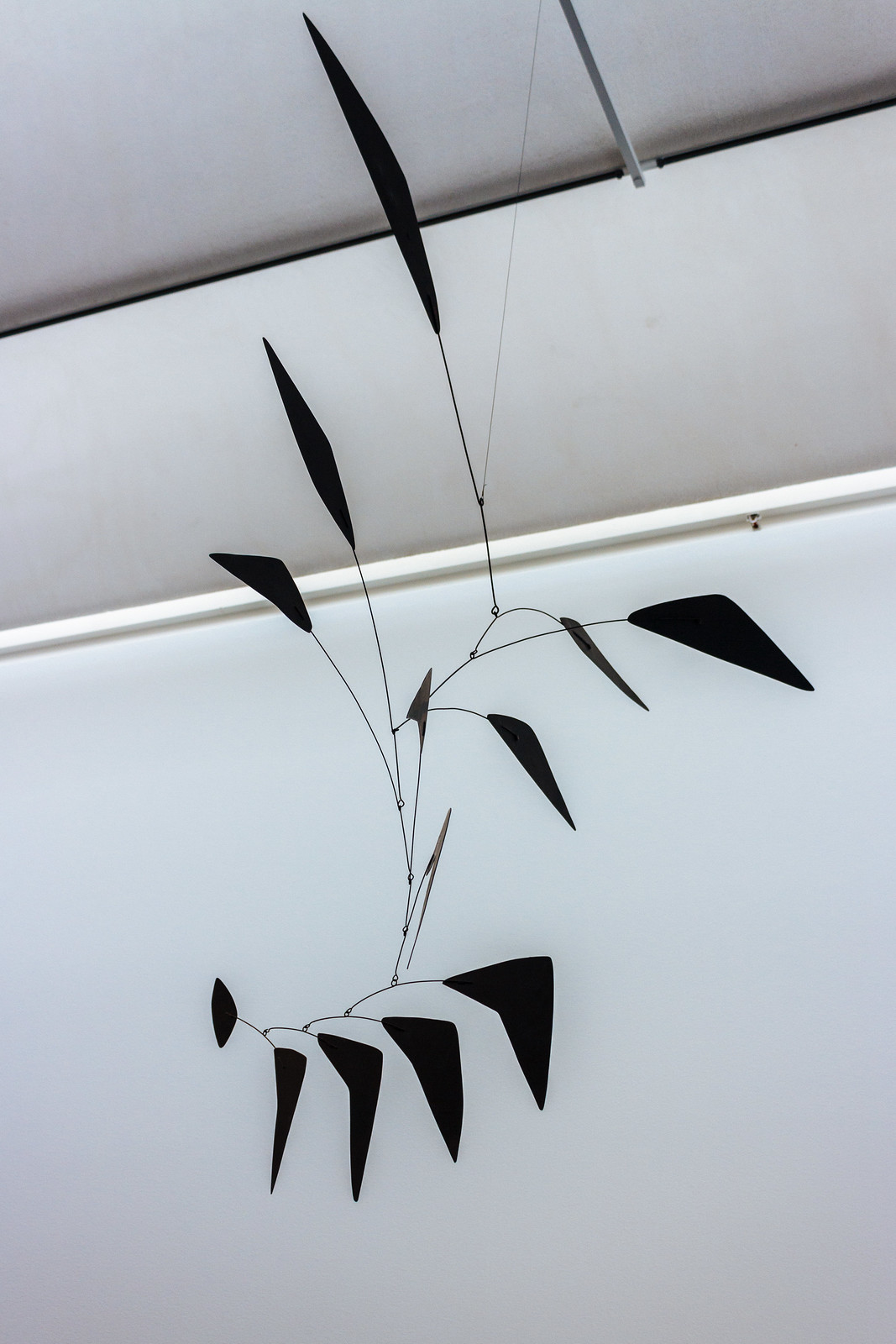 Modern art-style mobile featuring multiple black triangles, hanging from the ceiling