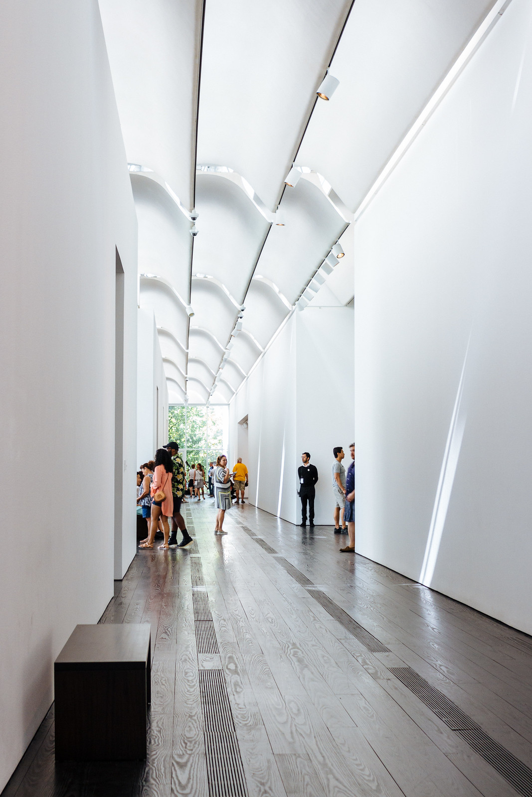 Museum hallway with plain white walls and curved ceiling tiles letting sunlight in