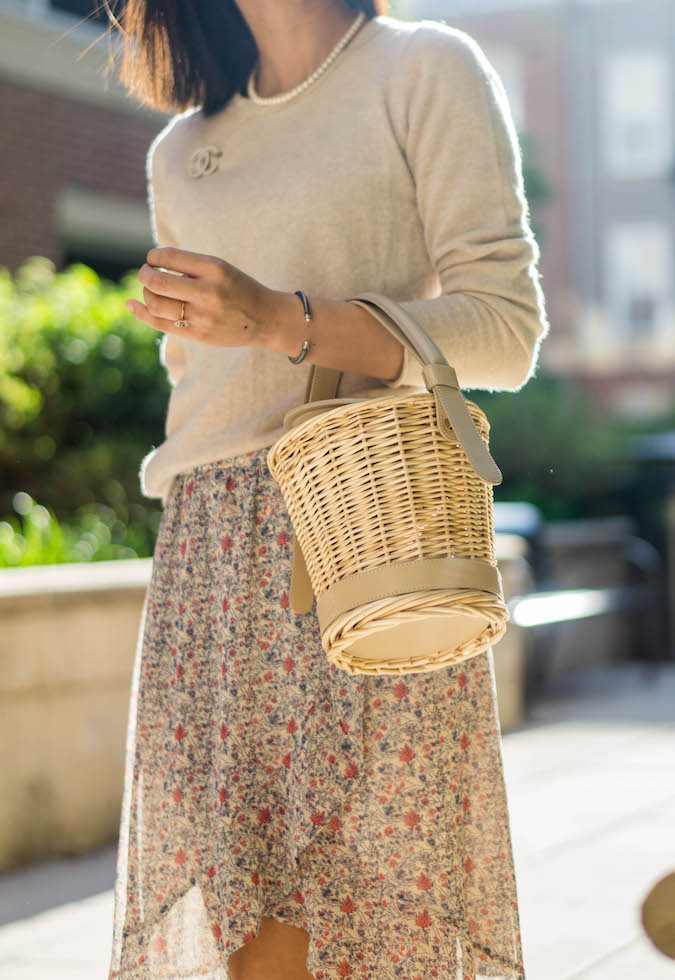 pearl necklace, Chanel 18P crystal/pearl brooch, Polene L'Osier wicker basket in sand, Madewell floral wrap skirt, David Yurman classic bangle