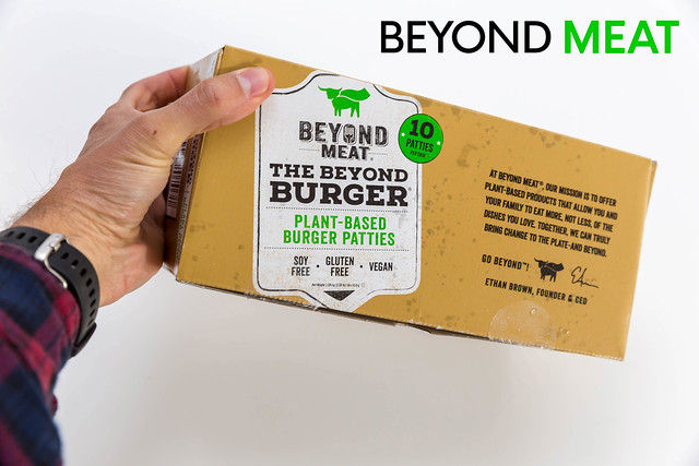 Man hold the veggie Beyond Meat Burger Box, with ten Patties, frozen packed, for a meatless, vegan diet without soy and gluten, in front of white background