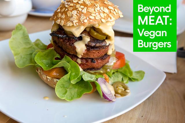 Gesunder Burger von Beyond Meat Burger, für eine vegane Ernährung, angerichtet im Burgerbrötchen, mit Sauce, Salat, Gurken, Tomaten und Zwiebeln