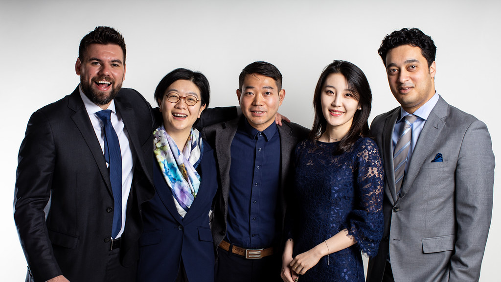 A group of MBA students stand together in a studio and smile at the camera.