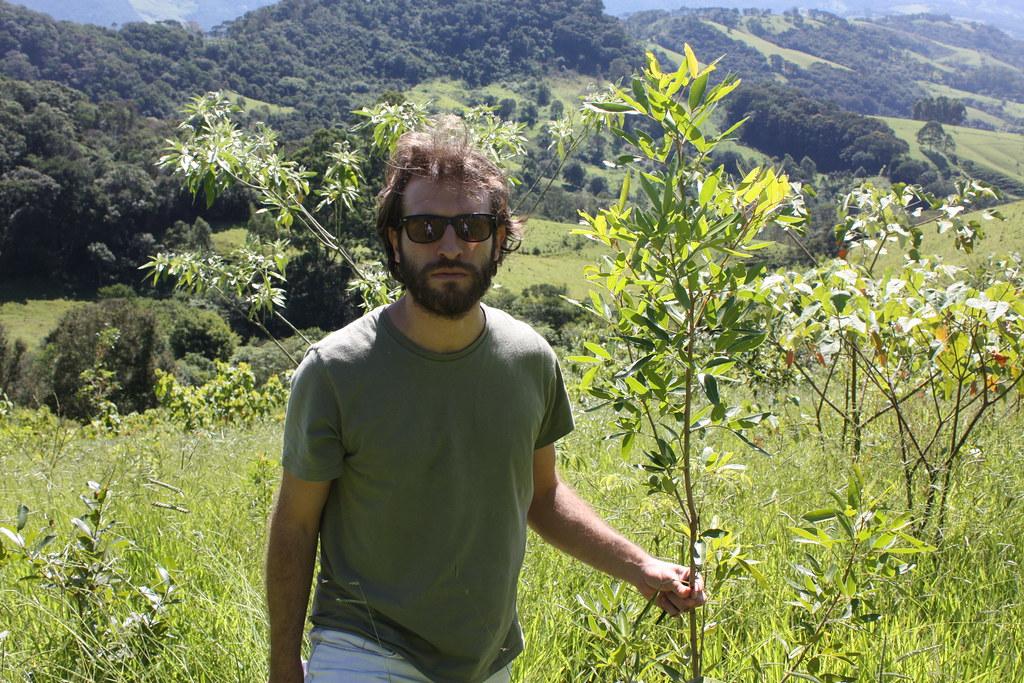 Lucas Carvalho diretor da Iniciativa Verde posa ao lado de muda em desenvolvimento