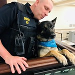 April 8, 2019 - 15:04 - On duty in the lobby of the Chester County (Pa.) Justice Center, Cpl. Matthew Mendenhall is joined by his K-9 partner, Nero, who sports a teal bandana to observe Sexual Assault Awareness month.