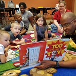 "September 8, 2017 - 11:14 - Miscellaneous Category Second Runner-Up  Photographer:  Lt. Bill Davis  Date Taken:  Sept. 8, 2017  Brief Description:  Deputy Rod White with the Bossier Parish Sheriff's Office reads the book, ""Too Many Toys,"" to children at the Benton Library in Benton, La., on Sept. 8, 2017.  Building and fostering relationships between deputies and children is an investment in the future.        Names of Individuals in the Image:  Deputy Rod White of the Bossier Parish Sheriff's Office and kiddos and parents.  Sheriff's Office:  Bossier Parish Sheriff's Office Parish and State:  Bossier Parish, Louisiana"