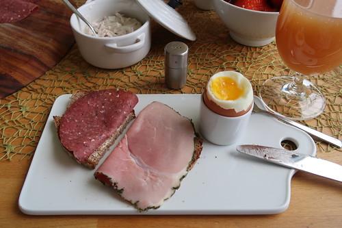 Dauerwurst mit zerstoßenem Pfeffer und Kochschinken mit Kräuterrand auf Holzofenbrot zum Frühstücksei