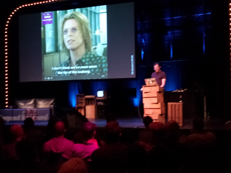 Tantek at the podium on stage at the start of his talk Take Back Your Web, showing a video of a 1999 interview of David Bowie about the internet