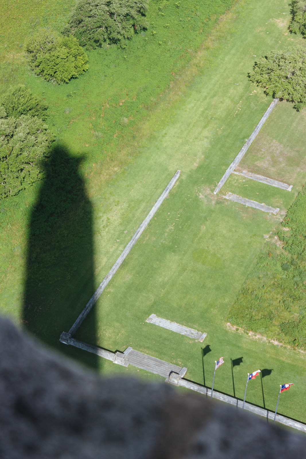 Shadow of a stone column on a grassy field with three flags seen from above