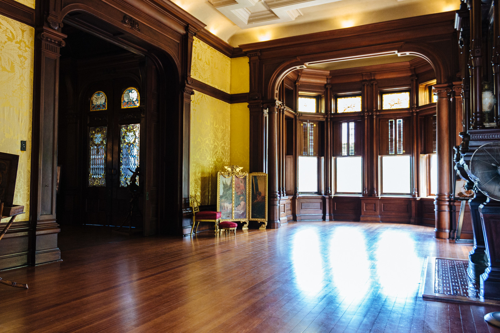 Room inside a mansion with wooden floors, large windows, and golden wallpaper