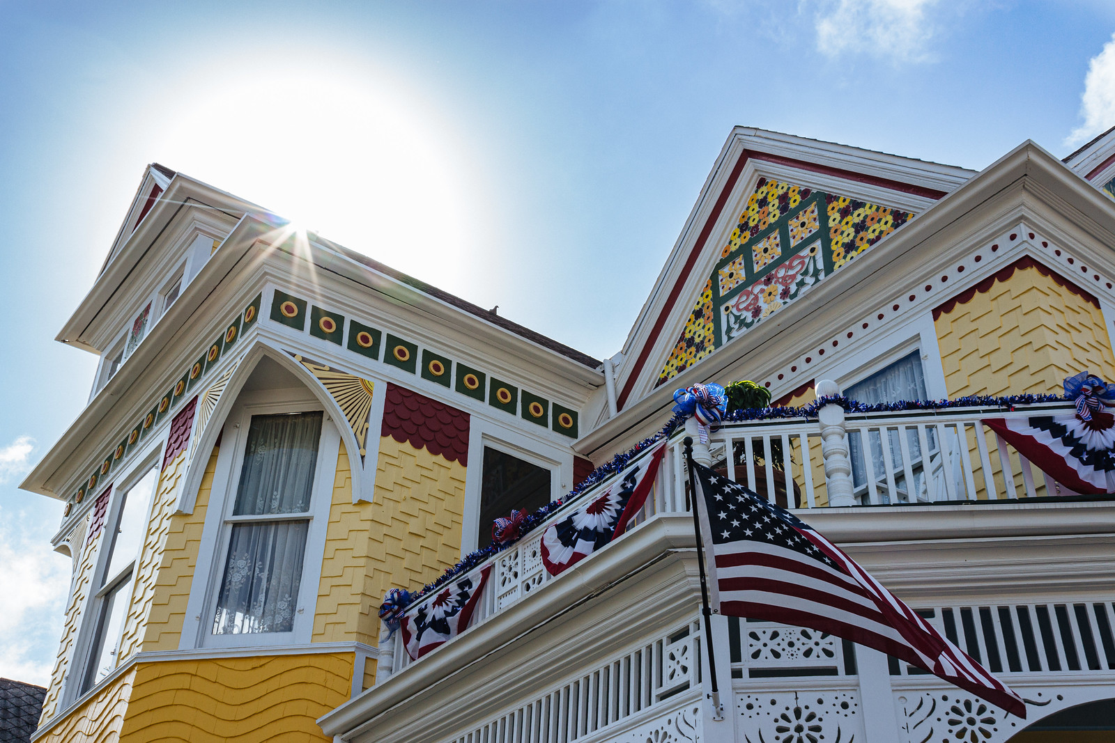 Victorian home with yellow singles on the walls and patriotic banners and flags