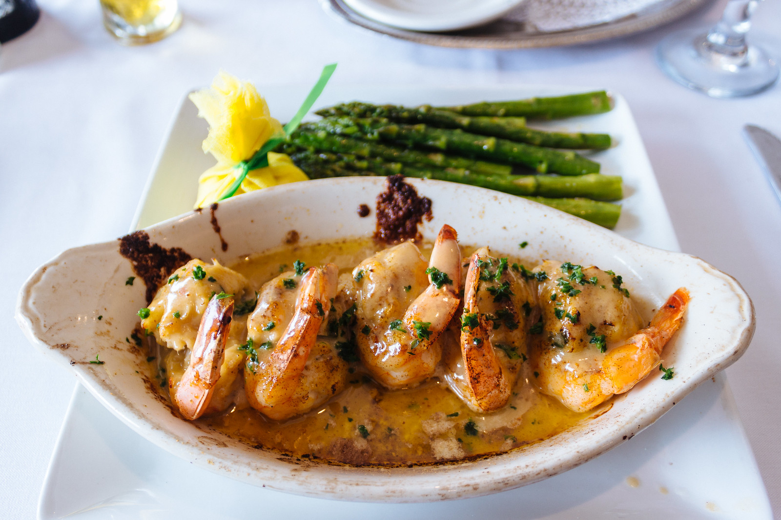 Bowl of five crab-stuffed shrimp with asparagus
