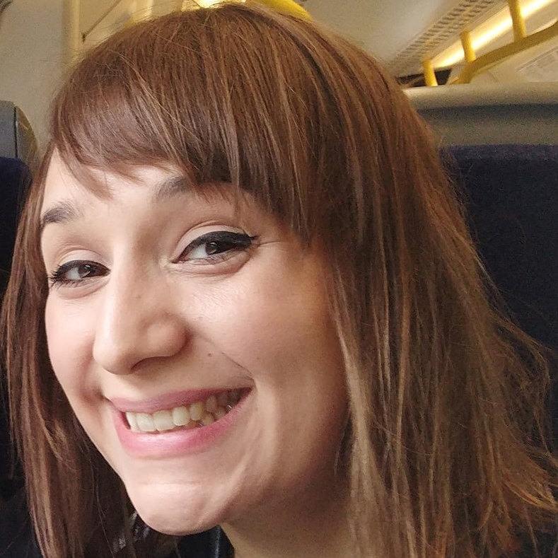 Selfie of Dr Emily Collins sat on a train.
