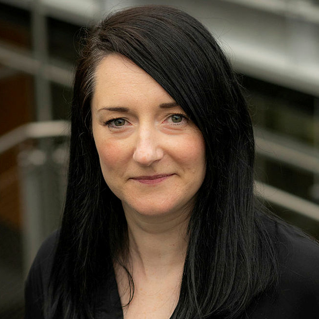 Photograph of Dr Joanne Hinds wearing a black top looking at the camera whilst stood in front of a staircase in an office building.