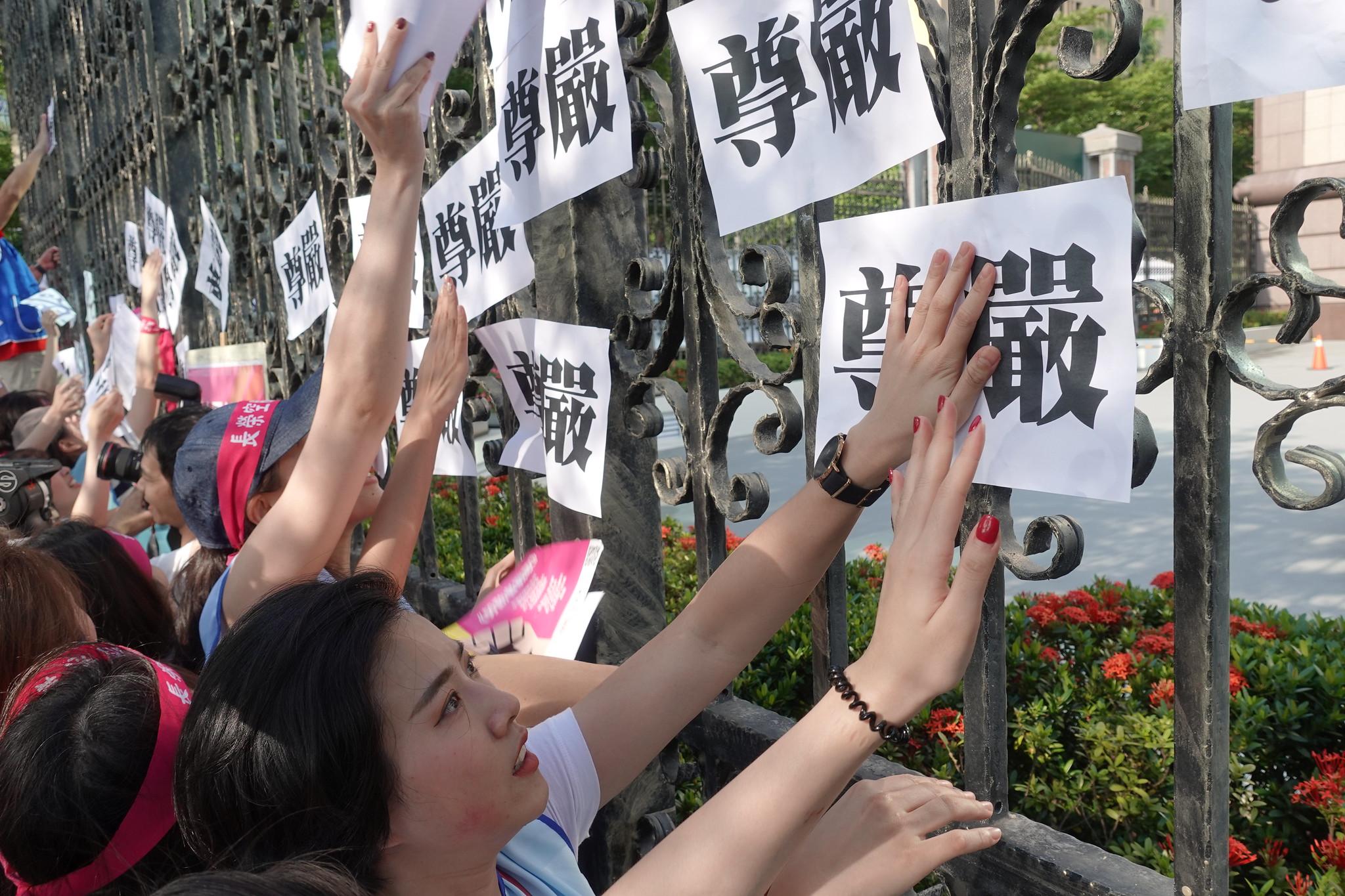 空服員在張榮發基金會圍牆貼上「尊嚴」兩字,反對公司威權管理,要求改善勞動條件。(攝影:張智琦)