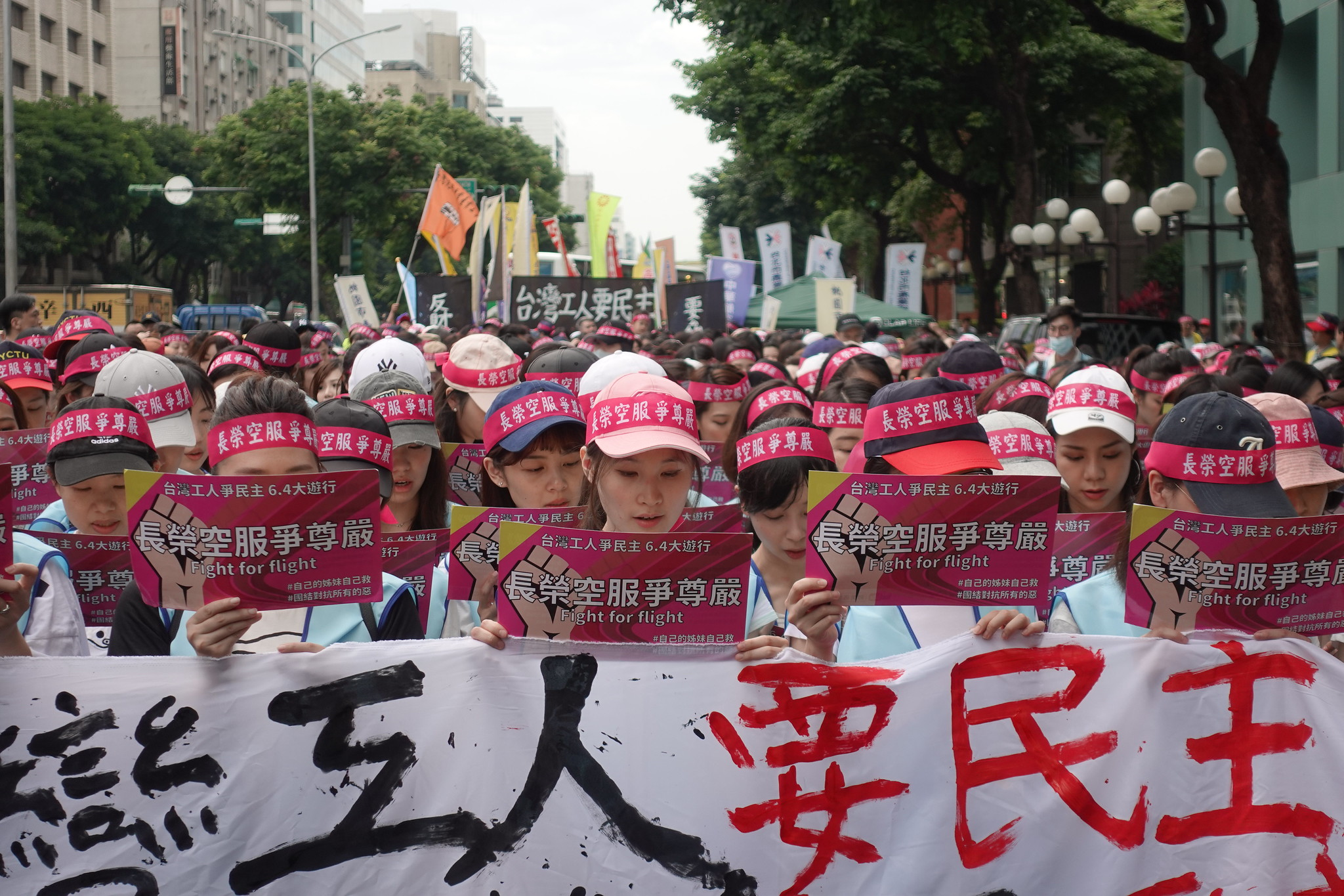 遊行前,長榮空服員在公司外合唱《美麗島》,希望台灣除政治民主外也能落實產業民主。(攝影:張智琦)