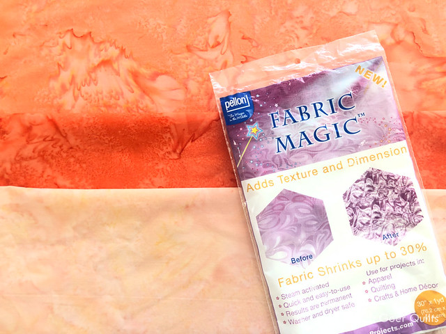 coral, flame, and peach colored batik fabrics with a package of Fabric Magic by Pellon