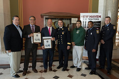 From left - Pat Cannon, V.P. of New Haven Firefighters, IAFF, Local 825, State Reps. John Fusco and Craig Fishbein, Frank Ricci, battalion chief and President of New Haven Firefighters, IAFF, Local 825, Josh Miller, V.P. of the New Haven Emerald Society, and firefighters Fernando Ramirez, of Truck 2, and Daniel Brown, of engine 11, pose for a photo after presenting citations to the Reps.  The New Haven firefighters recognized the legislators for their work on behalf of firefighters across the state during the annual New Haven Pizza Lobby Day at the Capitol.