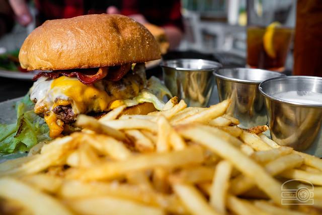 Burger w/ swiss, provolone, cheddar, seasoned lettuce, bacon and garlic aioli - Table 9