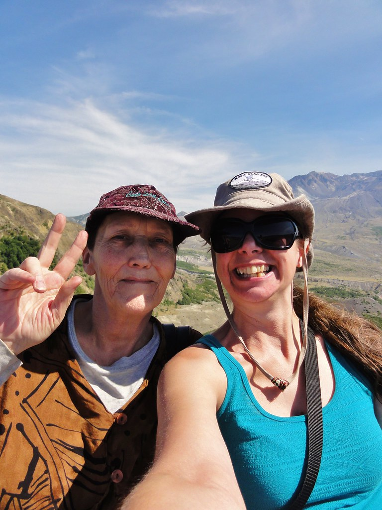 Image shows Suzanne, wearing a glittery ball cap and flashing a peace sign, and me taking a selfie with Mount St. Helens behind us.