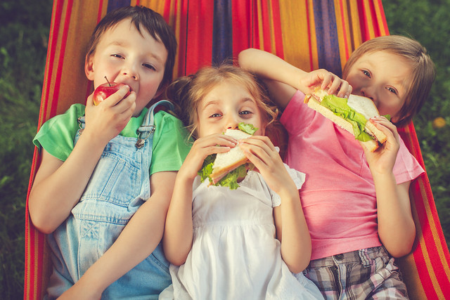 Three happy children eating apple and sandwiches in hammock