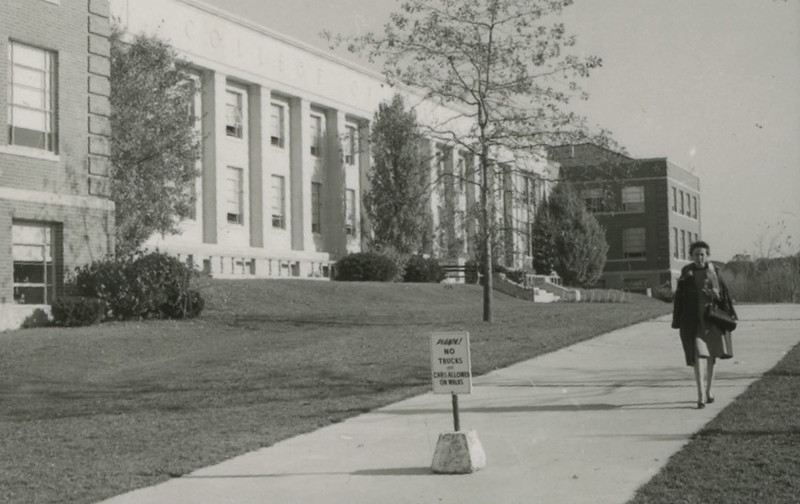 Woman walking in front of the W.B. Young building.