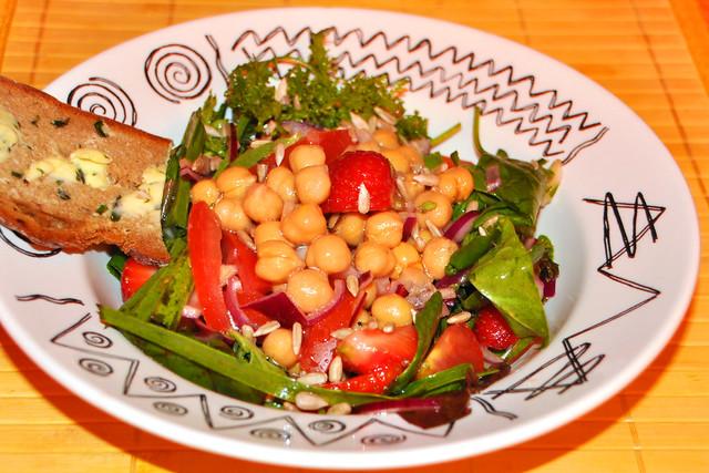 grünen Salaten, Kräutern, Kichererbsen, Tomaten, Zwiebeln und Knoblauch. Dazu ein Bärlauchbutterbrot.
