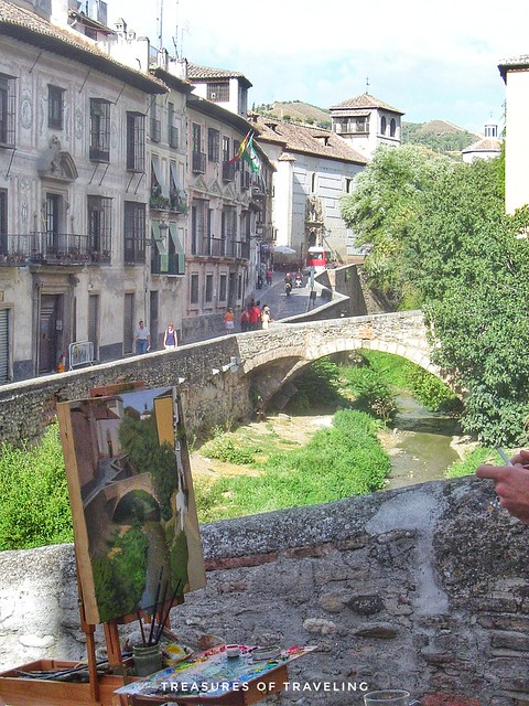 An artist painting a beautiful river scene from along the Carrera del Darro, which is a road that runs along the Darro River in the Albaicín. As you walk along the road don't forget to look up to see the Alhambra, which sits on top of the hill right acros