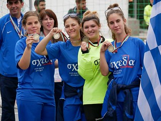 Women's homeless world cup team stood holding their medals and smiling