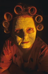 Woman at dining room table with facial mask and hair in curlers